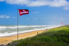 NO SWIMMING Flags Flying - Rough Surf on OBX. Beautiful sunny day at the beach on the Outer Banks of North Carolina, but rough surf keeping everyone out of the stock photo