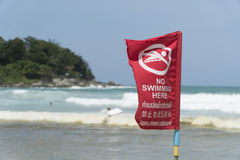 No swimming here sign dangerous area of the beach. Red flag in English and Thai text Royalty Free Stock Images