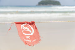 No swimming here sign dangerous area of the beach. Red flag in English and Thai text Stock Photography