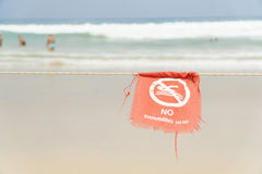 No swimming here sign dangerous area of the beach. Red flag in English and Thai text Royalty Free Stock Photography