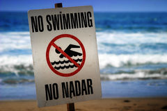 No swimming sign. On a beach with waves in the background Royalty Free Stock Photos