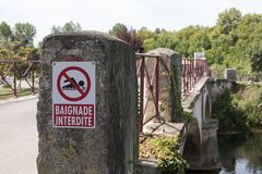No Swimming sign on bridge in France. No Swimming sign in French, on a bridge over a tributary of the Charente in Jarnac, France Stock Photos