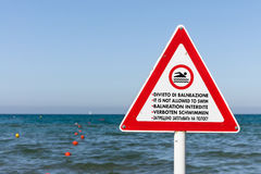 A no swimming sign on a pole in 5 languages Royalty Free Stock Image