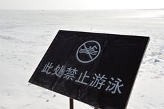 A no swimming signboard with a freezing lake Stock Photography