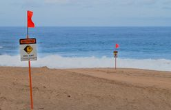 Warning Sign High Surf Rip Tide. No swimming. No wading. No surfing. Warning the beach area has high surf. Large sneaker-waves come in quickly without warning stock image