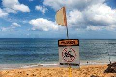 No swimming warning sign and red flag on the beach in Haleiwa stock photography