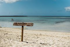 No Swimming Zone sign in tropical beach. A no swimming zone sign on a tropical beach in the Caribbean royalty free stock images