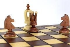 No tabuleiro de xadrez, a rainha e dois cavalos anunciaram uma verificação e uma esteira ao rei branco imagens de stock royalty free