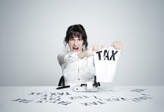 No tax!. Young desperate woman at her paperwork-covered desk ripping up a tax form staring at the camera stock photography