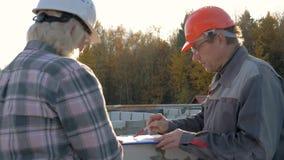 No telhado os trabalhadores da construção no capacete discutem a construção de acordo com o plano video estoque