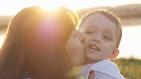 No tempo da noite antes do por do sol, do sentimento do bebê feliz e dos sorrisos com sua mãe no jardim Foto de Stock Royalty Free