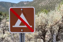 No camping sign. Sunny day in the desert in background. No tent camping sign on a sunny day in the desert in background royalty free stock image