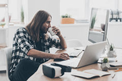 No time for break. Handsome young man with long hair working on the computer and drinking coffee while sitting at his desk in creative office Royalty Free Stock Photo