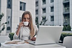 No time for break. Beautiful young woman writing something and drinking coffee while sitting in the modern restaurant stock photos