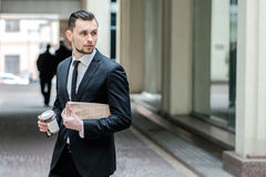 No time to rest. Confident businessman holding a newspaper and c Stock Images