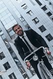 No traffic. Handsome young man in full suit smiling and looking forward while cycling outdoors Royalty Free Stock Photos