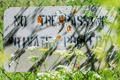 No Trespass behind grass. No trespass sign behind grass with bullet marks royalty free stock photo