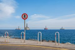 No trespass sign at end of road with ocean background,. Offshore drilling ships and platform on horizon stock images