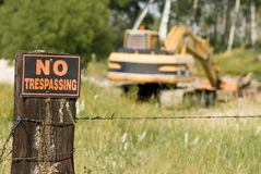 No Trespassing. At this work site featuring the sign and an excavator Royalty Free Stock Photos
