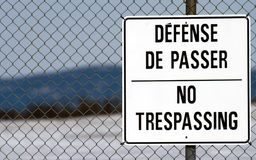 No trespassing. Close-up of a bilingual no trespassing sign with a fence background Stock Images