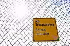 No Trespassing. English and French worn out bilingual warning sign on chainlink fence shot agains the sun Stock Photo