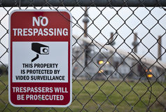 No Trespassing. A close up shot of a No Trespassing Sign on a fence with a power plant in the background Royalty Free Stock Image