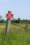 No Trespassing. A 'No Trespassing sign hangs on a post in deep grass Royalty Free Stock Photography
