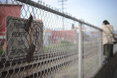 No trespassing. Private property no trespassing sign in foreground and woman climbing fence in background Stock Photo