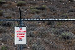 No trespassing authorized personnel sign on a chain link barbed wire fence royalty free stock photography