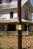 No trespassing posted sign. An old abandoned house with posted sign on pole royalty free stock image