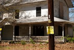No trespassing posted sign. An old abandoned house with posted sign on pole stock images