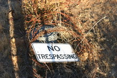 No trespassing sign. Closeup of no trespassing sign with barbed wire in countryside royalty free stock photography