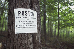 No trespassing sign. On tree at edge of forest Stock Photo