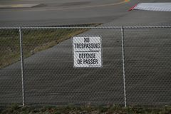 A no trespassing sign on a fence. Outside an airport on a spring day Royalty Free Stock Photos