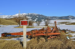 No trespassing sign in a field with an old item of machinery. Below the mountain range and field of snow is a field is an old cultivator with a No Trespassing stock photos