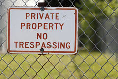 No Trespassing sign horizontal. A landcape photo of a stark red and white private property sign complete with chain link fence royalty free stock photo