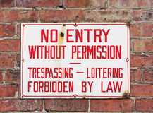 No trespassing sign mounted on brick wall Stock Images