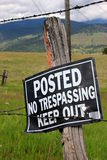 No trespassing sign. On a old, rustic wood post with rural background Royalty Free Stock Images