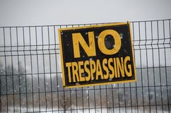 No Trespassing Sign. A sign that reads No Trespassing affixed to a wire fence danger private warning symbol background property metal safety caution black white stock photos