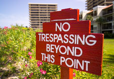No Trespassing sign in red by flower gardens Stock Image