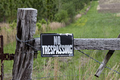 No trespassing sign on weathered fence post in front of a green Royalty Free Stock Images