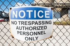 No trespassing warning sign on chain link fence stock photography