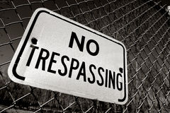 No Trespassing Warning Sign on Security Fence. Posted no trespassing warning sign on chain link wire security fence at restricted area Royalty Free Stock Image