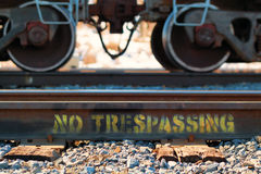 No Trespassing. Written on tracks with train wheels on top Royalty Free Stock Images