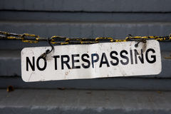 No tresspassing sign on chain. Beat up no trespassing sign hanging on chain Stock Image