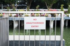 No unauthorised entry sign on the gate. No unauthorised entry sign on the stainless gate with water background stock photo