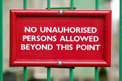 No unauthorised persons. Red No Unauthorised Persons sign on green railings with blurred background Royalty Free Stock Photo