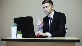 No, uomo d'affari che rifiuta scuotendo testa, mentre lavorando al computer portatile archivi video