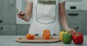 No vídeo moderno da cozinha a captura de uma mulher cortou uma pimenta doce alaranjada na frente do close up da câmera 4K vídeos de arquivo