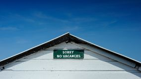 No vacancies sign set against deep blue sky. No vacancies sign on beach hut wide angle view with lots of blue sky Stock Photo